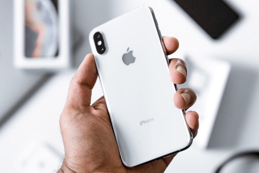 Come passare da Android ad iPhone. Mano che regge iPhone. Sullo sfondo altri dispositivi e accessori.